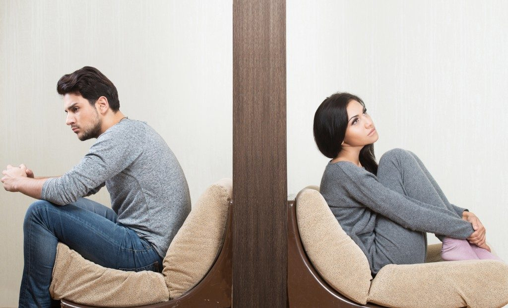 Man and woman sitting and facing opposite directions