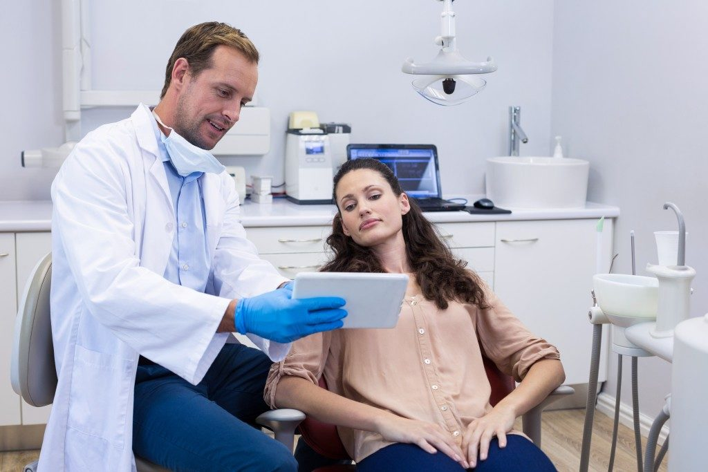 Dentist showing results to his patient