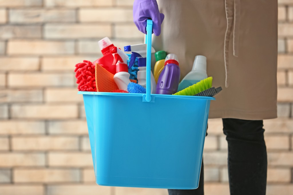 person carrying a bucket of cleaning materials